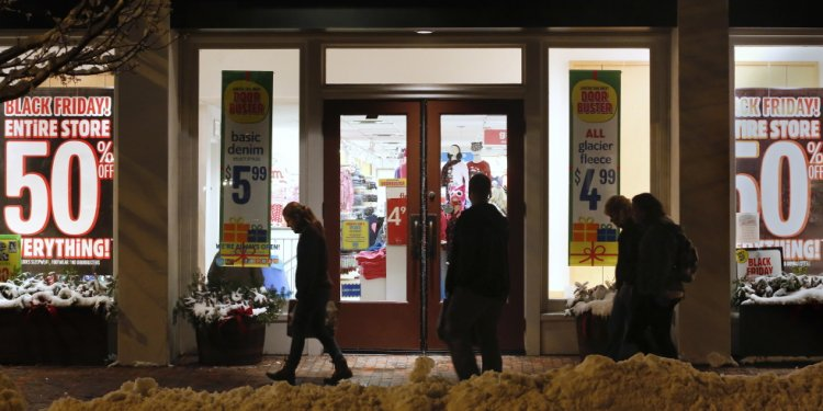 Shoppers pass by store windows